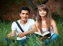 2 студента изучая в парке на траве Стоковая Фотография RF