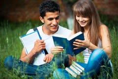 2 студента изучая в парке на траве Стоковые Фотографии RF