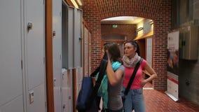 2 студента идя вниз с прихожей к шкафчику сток-видео