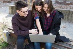 3 студента подростка средней школы с компьтер-книжкой Стоковые Изображения