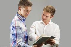2 студента смотрят книгу Стоковая Фотография