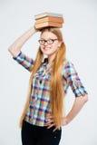 Студентка держа книги на голове Стоковая Фотография