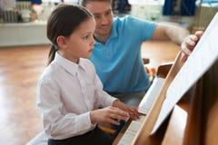 Студентка наслаждаясь уроком рояля с учителем стоковое фото