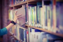 Студенты вручают с книгой рудоразборки smartwatch от книжных полок стоковые изображения rf