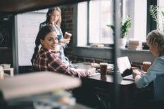 Студенты девушек выпивая кофе и изучая совместно на таблице Стоковые Изображения