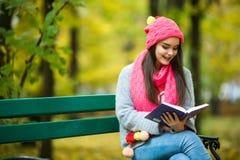 Студенты девушки прочитали книгу в желтом парке осени Стоковые Изображения RF