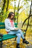 студенты девушки работая на компьтер-книжке в парке осени Стоковое Фото