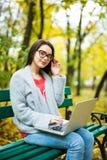 студенты девушки работая на компьтер-книжке в парке осени Стоковое Изображение RF