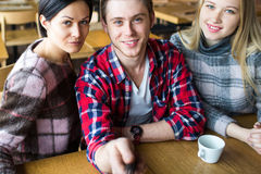 Студенты делают selfie в кафе Мальчик и 2 девушки делают selfie в кафе Стоковое фото RF