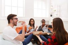 Студенты деля партию пиццы дома Стоковая Фотография