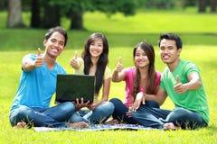 Студенты изучая в парке используя портативный компьютер стоковое изображение