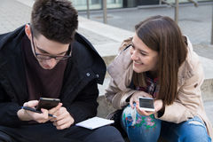 Студенты коллажа девушки и мальчика с умными телефонами в кампусе Стоковое фото RF