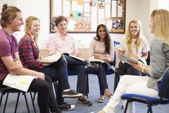 Студенты колледжа при гувернер имея обсуждение стоковое фото rf