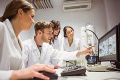 Студенты науки смотря микроскопическое изображение на компьютере Стоковое фото RF