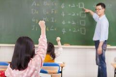 Студенты начальной школы поднимая руки стоковое изображение rf