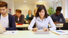 Студенты печатая на планшете и компьтер-книжке видеоматериал