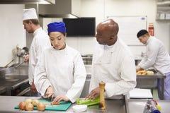 Студенты порции учителя тренируя для работы в ресторанном обслуживание стоковая фотография rf