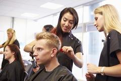 Студенты порции учителя тренируя для того чтобы стать парикмахерами стоковое изображение rf