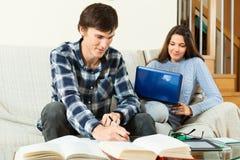 Студенты подготавливая для экзамена с книгами и тетрадью Стоковая Фотография