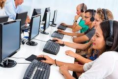 Студенты по обмену работая на компьютерах. стоковое изображение