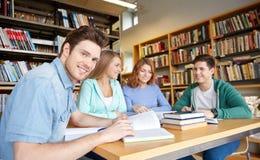 Студенты при книги подготавливая к экзамену в библиотеке Стоковая Фотография