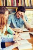 Студенты при книги подготавливая к экзамену в библиотеке Стоковая Фотография RF