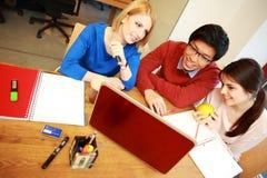 Студенты работая на компьтер-книжке совместно Стоковые Изображения RF