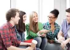 Студенты связывая и смеясь над на школе Стоковые Изображения RF
