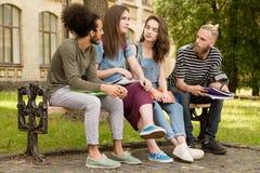 Студенты сидя на стенде говоря рассказы Стоковая Фотография