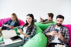 Студенты сидя на стульях погремушкы и изучая и используя smartphones в студии Стоковые Изображения