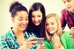 Студенты смотря smartphone на школе Стоковые Фотографии RF