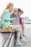 Студенты университета изучая пока сидящ на низкой стене в парке Стоковые Изображения