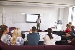 Студенты университета присутствуя на лекции на кампусе стоковые фотографии rf