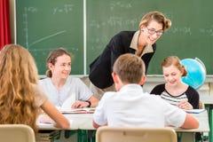 Студенты учителя уча уроки землеведения в школе Стоковая Фотография