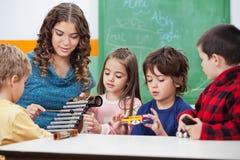 Студенты учителя уча для того чтобы сыграть ксилофон внутри Стоковая Фотография RF