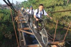 Студенты школы идут к школе через висячий мост Стоковое фото RF