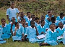 Студенты школы сидят на земле и ждут школьный автобус Стоковые Изображения