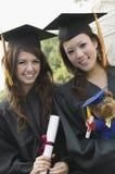 2 студент-выпускника держа портрет диплома и плюшевого медвежонка Стоковые Фото