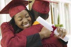 2 студент-выпускника обнимая снаружи Стоковая Фотография
