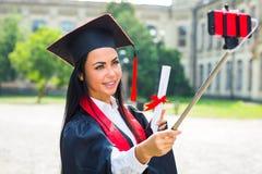 Студент-выпускник девушки получает фото selfie с smartphone Стоковая Фотография