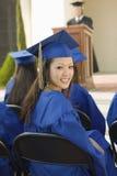 Студент-выпускник женщины при друзья присутствуя на выпускной церемонии Стоковая Фотография RF