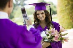 Студент-выпускник имея сфотографированный с мобильным телефоном снаружи Стоковое Изображение