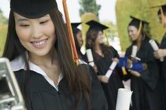 Студент-выпускник используя сотовый телефон снаружи с другими позади Стоковое Изображение