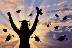 Студент-выпускник поднял его руки к небу и крышке и заходу солнца диплома постдипломной Стоковое фото RF