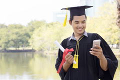 Студент-выпускник студента держа умный телефон Стоковые Фото