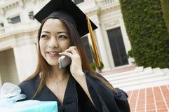 Студент-выпускник с подарком используя сотовый телефон снаружи Стоковая Фотография RF