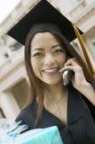 Студент-выпускник с подарком используя сотовый телефон Стоковая Фотография