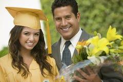 Студент-выпускник с цветками и отцом снаружи Стоковые Изображения RF