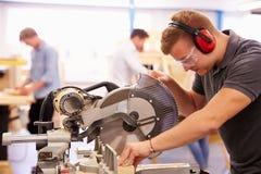 Студент в классе плотничества используя круглую пилу стоковая фотография