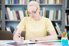 Студент в стеклах писать в библиотеке стоковая фотография rf